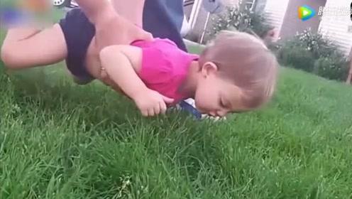 爸爸想把小屁孩放在草地上玩,不料宝宝不乐意立马做出反应,太逗了