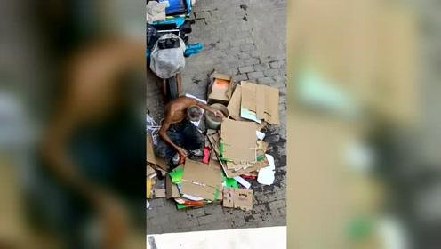 天太热了,收废品的大爷给纸箱撒点水,防止它中暑
