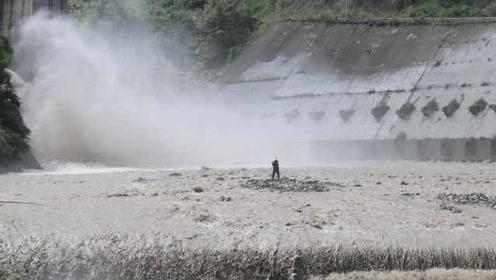 差1秒被吞没!68岁老人河中捡废铁遇洪水,冲下堤坝又爬起