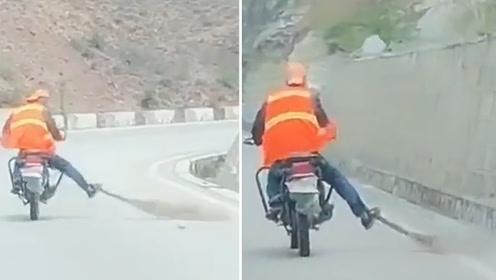 """实拍""""最牛""""扫路工人:一边骑摩托车 一边用脚清扫国道"""