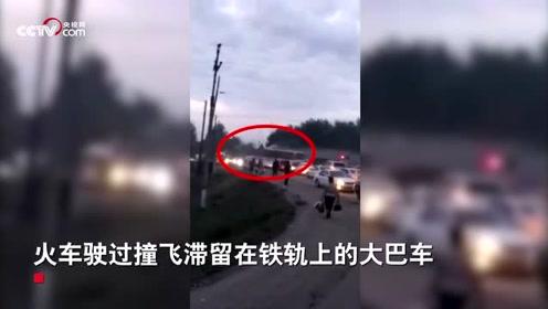 哈萨克斯坦一大巴车被堵在铁轨上 被火车撞飞