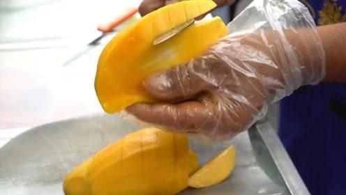 小摊老板切芒果,刀法让人眼花缭乱,来买的人不是为了水果