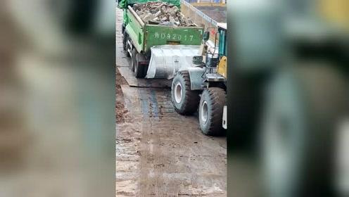 坡道上铺钢板,大货车上不去,装载机帮忙推车!