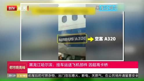 黑龙江哈尔滨:挂车运送飞机部件 因超高卡桥