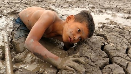 这里水都干涸了,小孩却在这里掏了满满一桶鱼
