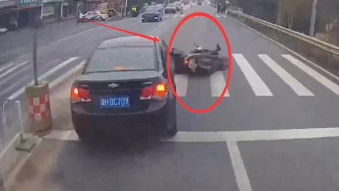 电动车过路口不看后车直接变道,被小汽车直接撞翻,场面残忍