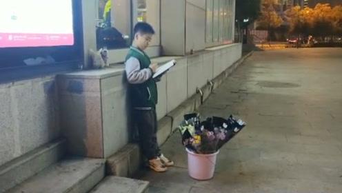 """南昌版""""凿壁偷光"""" !10岁小男孩地铁站旁卖花 还不忘借着灯光看书"""