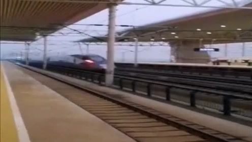 复兴号列车在雨中飞驰通过车站,一瞬间只能看到车尾灯了