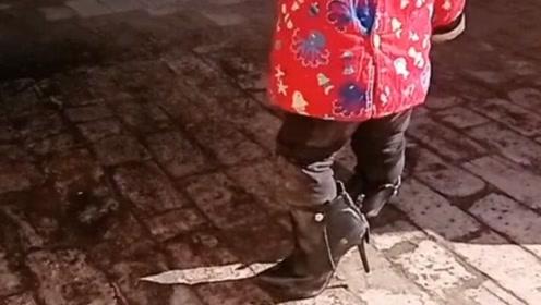 小家伙真是太调皮了,非要穿妈妈的高跟鞋!