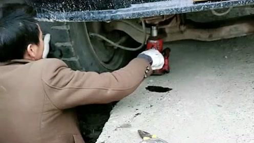 货车的轮胎掉进沟里了,司机拿个迷你千斤顶来用,看着好辛苦