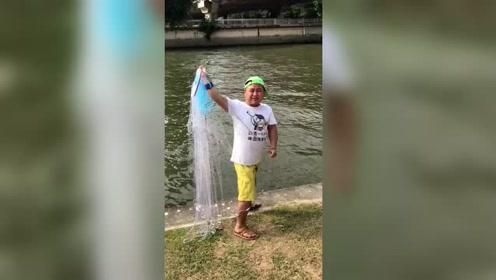 男子在河边撒网捕鱼,刚撒下网就收,结果收获几十斤