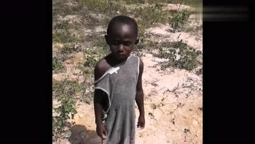 非洲小孩在烈日下站着也不怕晒,穿的衣服破破烂烂让人心疼!