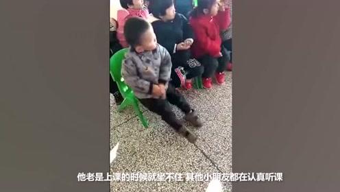 3岁萌娃教室内坐凳子上打拳 不受一旁同学影响不停比划拳脚