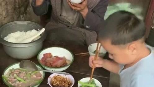饭桌上虽然有好几道菜,但只有小朋友在吃,别人都只吃自己碗里的米饭!