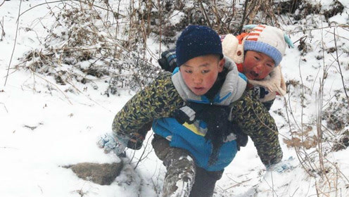 凉山男孩雪中背弟弟搬家 200米落差山路走50分钟