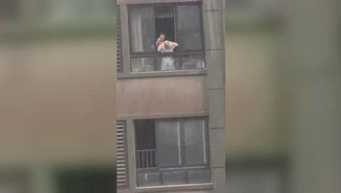 实拍西安遭遇瓢泼大雨 市民从阳台探出身子用雨水洗头
