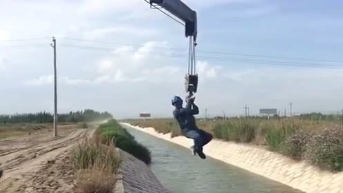 司机把吊车玩出新花样了,直接把人吊着过河,看把小伙乐的!