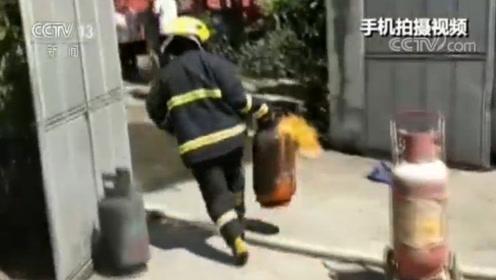 惊险 消防员拎喷火煤气罐奔跑