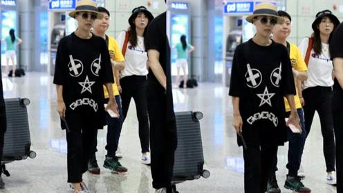 52岁那英穿宽松黑T戴草帽 手拿折扇悠闲自在走机场