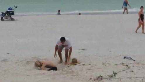 小伙陷入沙滩流沙!路人纷纷上前营救,这恶作剧太坏了
