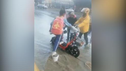 超暖!大雨致路段积水 外卖小哥用电动车为行人垫脚过马路