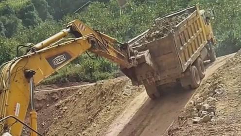 这个坡太陡了,每一车都要挖机在后面推才能上