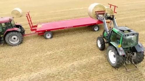 法国农场主一家人全出动,开着拖拉机去麦田运输麦秆草捆