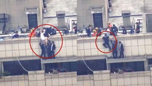 实拍:女子抱玫瑰爬上30楼楼顶欲自杀 辅警25秒托举生死救援