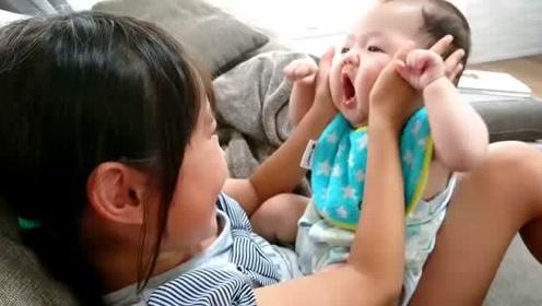 姐姐不停的挤弄宝宝小胖脸,把娃气的哇哇大叫要咬人,大人都笑疯了
