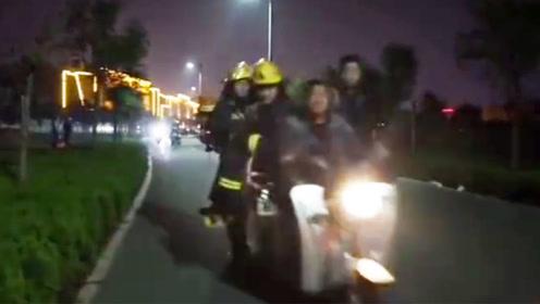 消防车出警被堵跑步前进 路人骑电动车载消防员救火