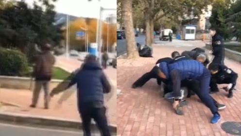 大连一男子手持菜刀街头与民警对峙,过路男子一个抱摔将其制服
