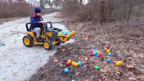 孩子们骑着拖拉机假装玩五颜六色的球
