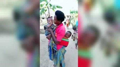 非洲黑人妈妈,背着1个,抱着1个,后面还有1个!4个儿子,幸福!