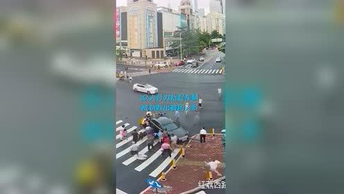 小车倒车压伤路人众人飞奔上前抬车救人