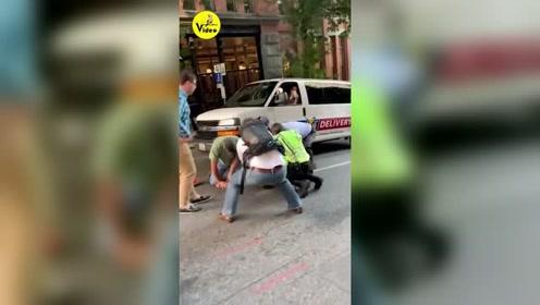 美国西雅图男子街头砸坏多辆汽车,路边围观群众合力将其拿下