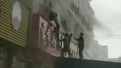 惊险一幕!旅馆2楼起火多人被困,街坊拦下货车搭梯救人
