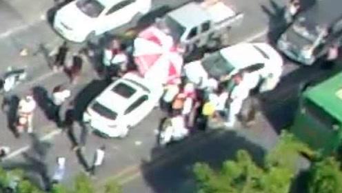 电动车被卡小车中间,路人纷纷抬车救人,还拿大伞为伤者遮阳