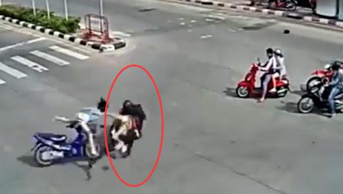 摩托车闯红灯,被正在直行的车辆连人带车猛然撞翻,现场一片狼藉
