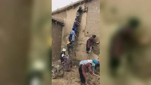 村民冒雪用泥巴抹墙建房,众人站在梯子上接力传递