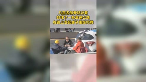 加泰抗议者封堵高速公路,支起桌子围坐打牌。