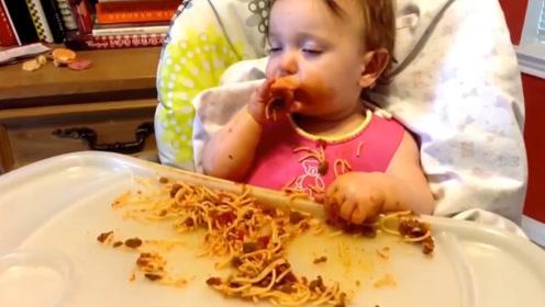 小宝宝吃饭时犯困了,迷迷糊糊的还不忘往嘴里塞面条,太可爱了