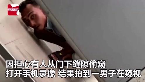 女子上厕所担心被偷窥打开手机录像,竟拍到男子从门下缝隙偷看