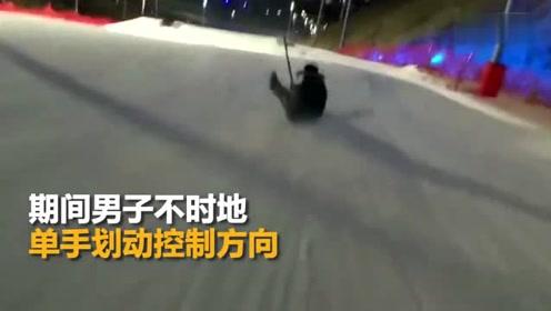男子坐铁锹高速滑下雪坡 漂亮转体也险些侧翻