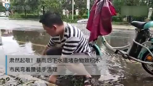 肃然起敬!暴雨后下水道堵杂物致积水 市民弯着腰徒手清理