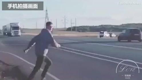 俄罗斯男子打赌认输  竟冲上马路躺在疾驰的货车下