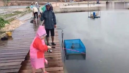 小女孩下雨天钓鱼,居然钓到了一条大鱼!