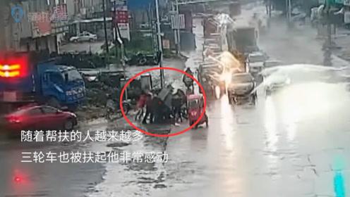 雨天三轮车侧翻驾驶员喊救命 小车司机下车招呼众人帮扶