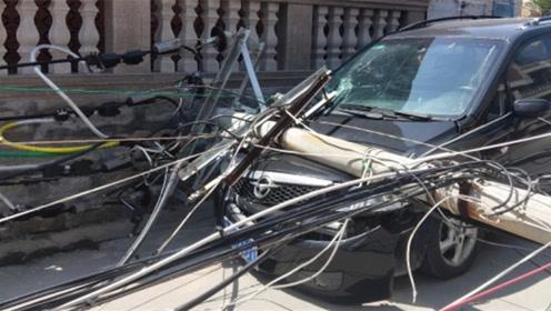 电线杆突然倒塌 停在路边的小车不幸被砸中