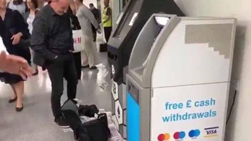 "ATM机""发疯""般狂吐一地钞票 取款人无奈用包接"