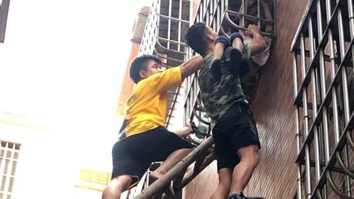点赞托举哥!男童头卡防盗网身体悬空,路人架梯托举救援